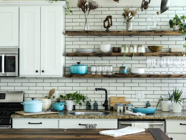 Wood floating shelves along the back of this kitchen wall.
